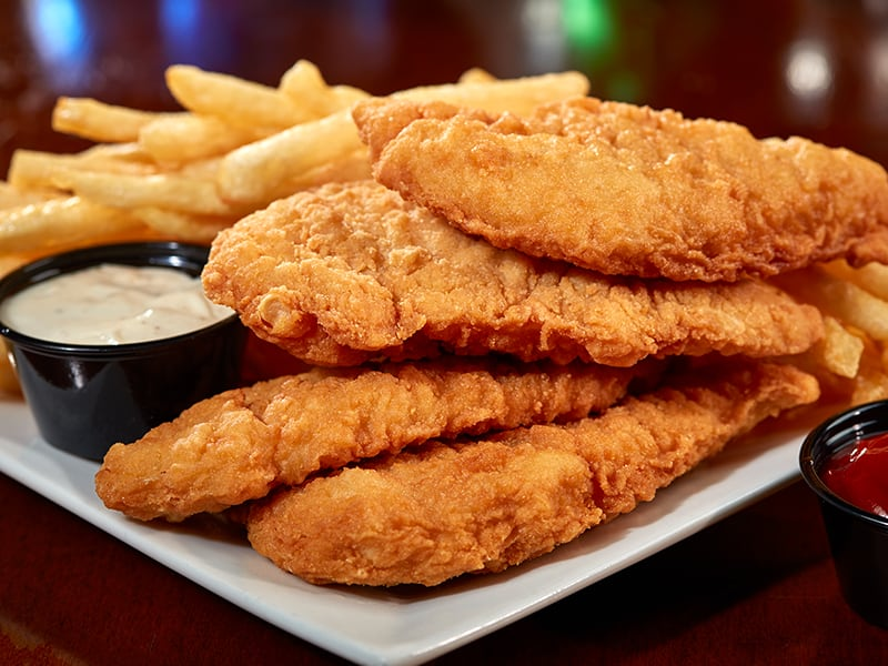Chicken tenders on a plate with fries and dip