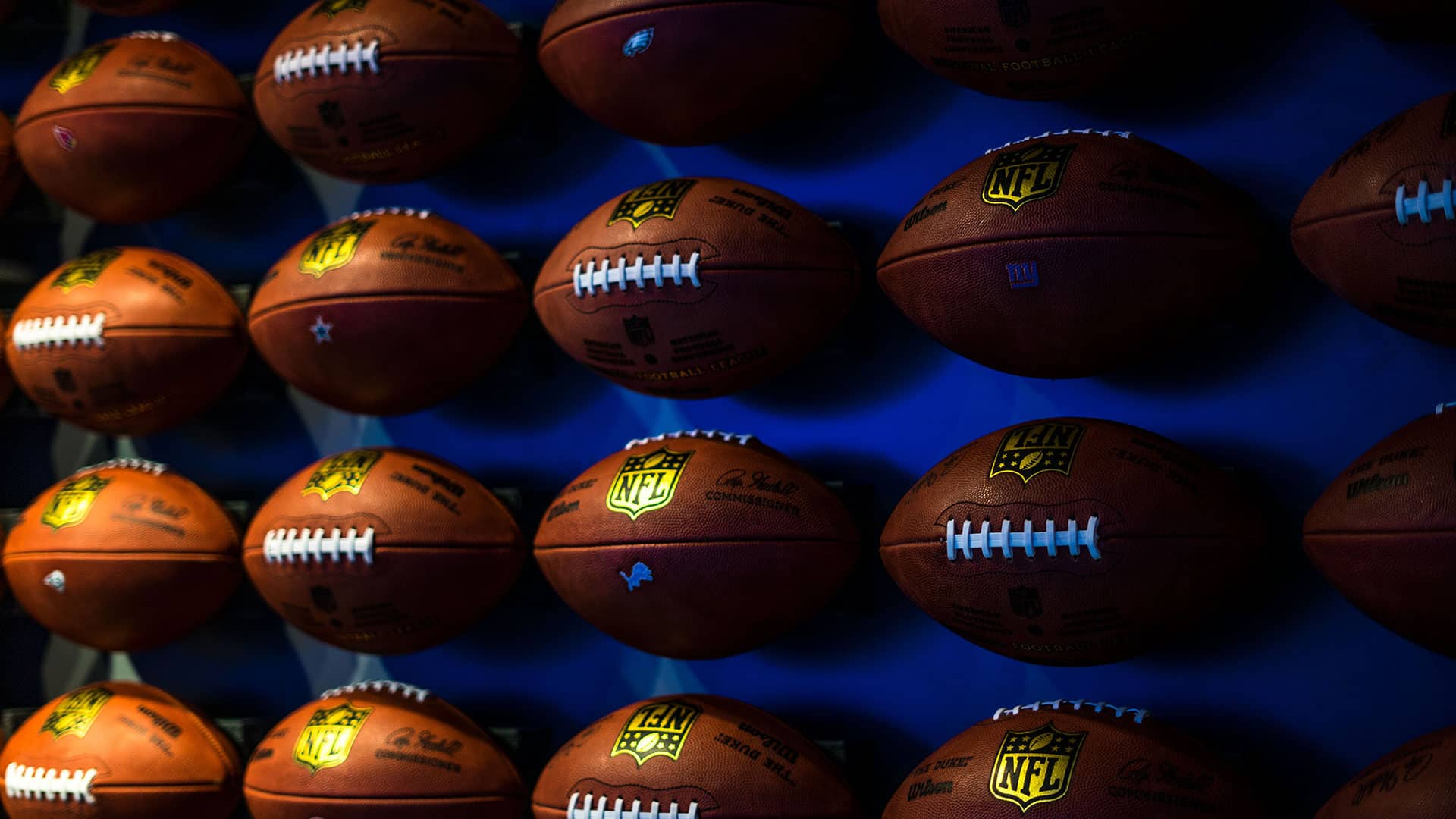 Footballs on a wall with a blue background